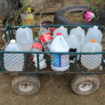 Old milk and bleach jugs serve as water containers for Elba Negron Carreras and her family. She and her two children walk a half-hour to the nearby water station and fill them up to use for showering and cooking when their tap water is not flowing. (Carmen Heredia Rodriguez/KHN)