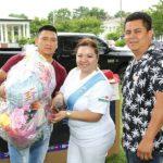 Jazmín Buke (centro) y Vani Hernández (dcha.) de la ZMX entregando uno de los premios donados a un participante en la rifa a beneficio de los damnificados del Volcán de Fuego en Guatemala