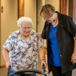 Janie York (right) walks with Elaine Martin down the hall at the SilverRidge Assisted Living facility in Gretna, Neb., on Aug. 15, 2018. York runs Hear Now mobile hearing solutions, a business aimed at cleaning hearing aids and checking the ears of older people living in residential care settings. (Chris Machian for KHN)
