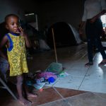 """Pierre watches as her 2-year-old son, Adrian, plays. """"When you have kids, you have to look for a better future for them,"""" she says. Pierre shares one of the tents in the background with her husband and two children. Sleeping on a hard floor with a few blankets is uncomfortable for her. """"When you're an immigrant and you're not working, it makes it hard to buy things that you need,"""" she says. She expects to wait at the shelter for at least two more months before she can appear before a U.S. immigration judge. """"Our number is 2,716."""""""