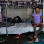 """Jimenez Martinez shares the lower level of a bunk bed with her husband in the shelter. """"It's hard to sleep because the babies move a lot and keep me up all night,"""" she says. Food isn't guaranteed at the shelter, so her husband cuts hair on the side to buy a little extra. """"I get cravings, but we don't have money for proper nutrition,"""" she says."""