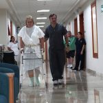 Physical Therapist Carlos Bauque helps Donna Ferguson walk as she recuperates from her surgery. (Rocco Saint-Mleux for Kaiser Health News)