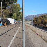 Large plastic tarps protect dilapidated camping tents on one side of the Atwater Village bike path, which runs alongside the Los Angeles River. (Anna Almendrala/Kaiser Health News)
