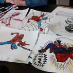 "Drawings made by Jenn and Jason's 15-year-old son lie on the family's dining room table in their home in central Illinois. Though his angry outbursts reveal a violent side, his parents say that most of the time he is ""kind, funny and smart"" — a teen who enjoys drawing pictures of superheroes. (Christine Herman/Illinois Public Media)"